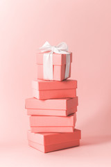 Close view the stack of boxes tied with silk ribbon, lying on each other on living coral color pastel background. Gift festive selection.