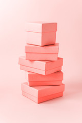 Close view the stack of boxes, lying on each other on living coral color pastel background. Gift festive selection.