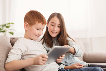 Happy siblings playing with pc tablet together