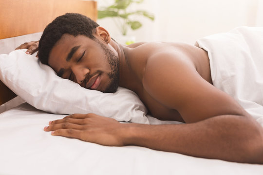 Naked black man sleeping in bed at home