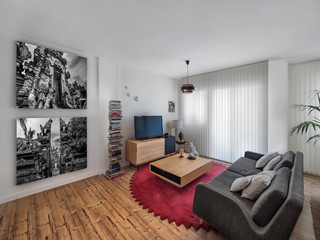 Modern interior decoration of a living room with a sofa, black and white posters, retro lamp, carpet, wooden floor, vintage wood chairs and table.