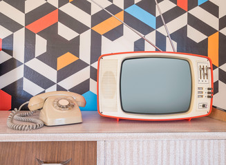 Retro television with vintage telephone and wallpaper in the background. Template interior decoration with ceramic decoration from the 70s