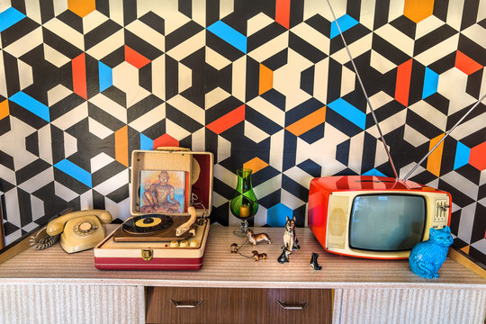 Vintage decoration with geometric wallpaper, retro tv, old portable record player, telephone and ceramic.