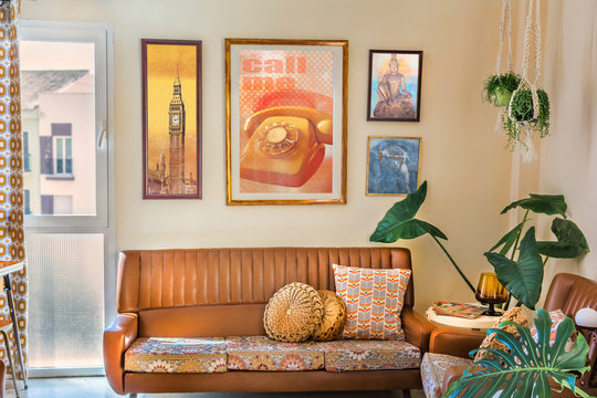 Vintage interior decoration with a retro sofa, old posters,  macrame plant hangers, retro print cushions.