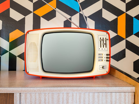 Retro television with vintage wallpaper in the background. Interior decoration from the 70s