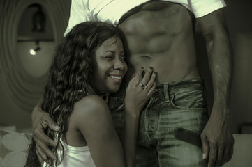 young happy and attractive black afro American couple the man showing sexy six pack abdomen and the woman playful proud and excited cuddling her lover in love and passion