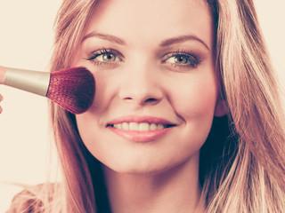 Smiling woman holding make up brush