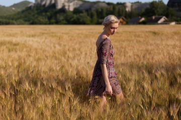 a woman farmer in a field of ripe wheat harvest