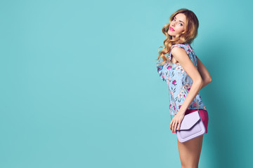 Young woman Smiling in Spring Summer Outfit. Pretty Blonde Girl in Fashion Stylish Floral Top, Trendy Wavy Curly Hairstyle. Beautiful Playful Model Having Fun