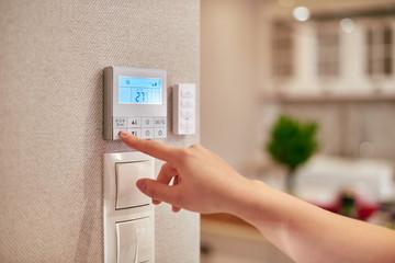 Obraz Woman programming temperature inside home - fototapety do salonu