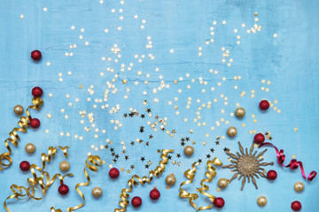 Colorful holiday decoration on blue background. Top view, copy space. Flat lay.