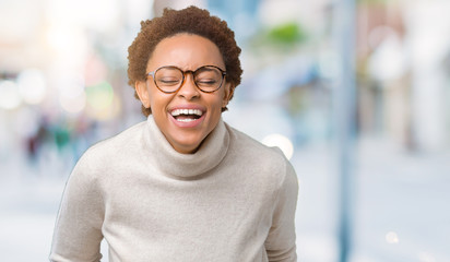 Young beautiful african american woman wearing glasses over isolated background Smiling and laughing hard out loud because funny crazy joke. Happy expression.
