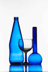 two blue bottles and a glass