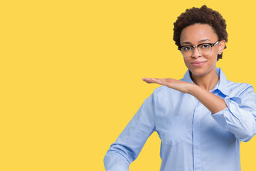 Young beautiful african american business woman over isolated background gesturing with hands showing big and large size sign, measure symbol. Smiling looking at the camera. Measuring concept.