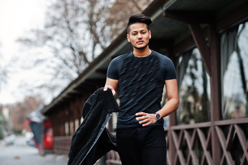 Handsome and fashionable indian man in black shirt with jacket posed outdoor.