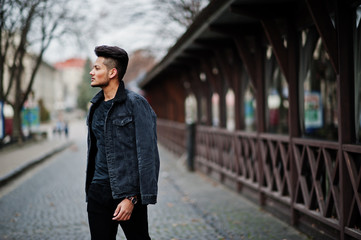 Handsome and fashionable indian man in black jeans jacket posed outdoor.