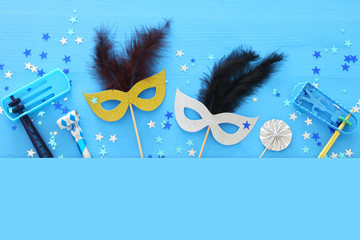 Purim celebration concept (jewish carnival holiday) over blue wooden background. Top view.