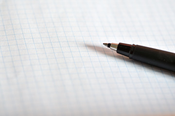 White notebook and black pen on white background