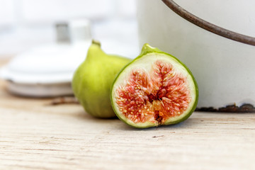 Ripe halved figs on old wood table with antique white enamel bucket