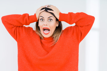 Young woman wearing casual red sweater over isolated background Crazy and scared with hands on head, afraid and surprised of shock with open mouth