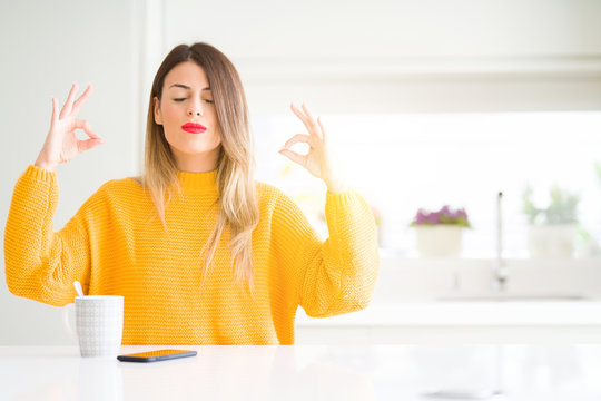 Young beautiful woman drinking a cup of coffee at home relax and smiling with eyes closed doing meditation gesture with fingers. Yoga concept.