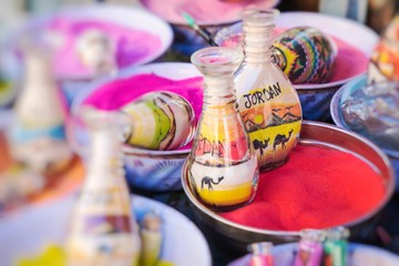 Souvenirs from Jordan - bottles with sand and shapes of desert and camels. Selective Focus.