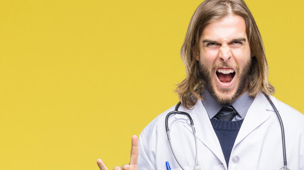 Young handsome doctor man with long hair over isolated background shouting with crazy expression doing rock symbol with hands up. Music star. Heavy concept.