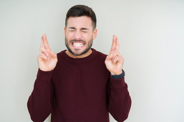 Young handsome man wearing a sweater over isolated background smiling crossing fingers with hope and eyes closed. Luck and superstitious concept.