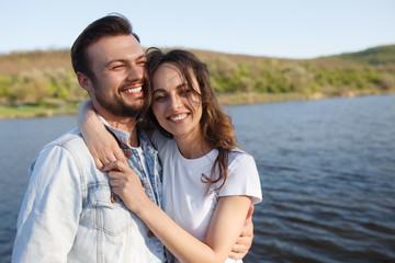Cheerful couple hugging near lake
