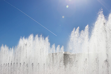 Fountain in the park on a background of blue bright sky with traces from the airplane