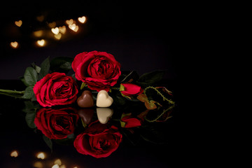 Red roses and heart shaped chocolate on black background
