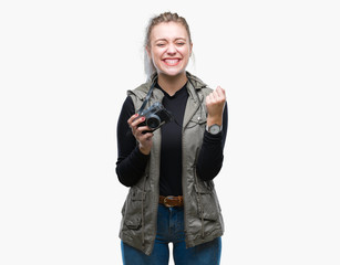 Young blonde woman taking pictures using vintage camera over isolated background screaming proud and celebrating victory and success very excited, cheering emotion