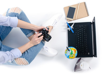 top view travel concept. Woman sitting and using laptop camera, smartphone, cup of coffee map and outfit of traveler business on white background with copy space