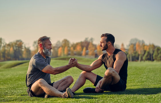 The old and young sportsmen handshaking on the grass
