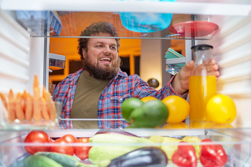Man looking for something to eat at night while standing in front of opened fridge. Unhealthy eating concept. Picture taken from the inside of fridge.