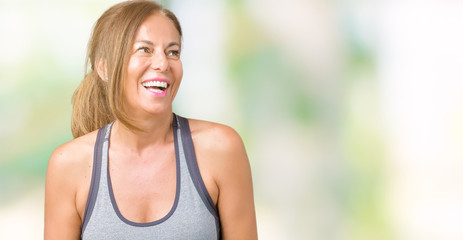 Beautiful middle age woman wearing sport clothes over isolated background looking away to side with smile on face, natural expression. Laughing confident.