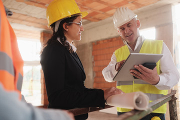 Architect Engineer And Manual Worker Meeting In Construction Site