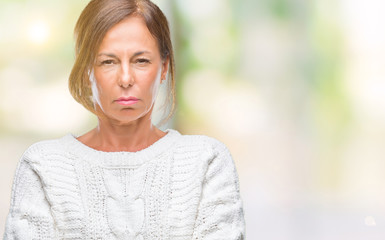 Middle age senior hispanic woman wearing winter sweater over isolated background skeptic and nervous, disapproving expression on face with crossed arms. Negative person.