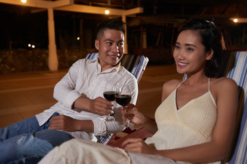 Happy young Asian couple sitting on lounger toasting with red wine and celebrating outdoors