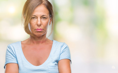 Middle age senior hispanic woman over isolated background skeptic and nervous, disapproving expression on face with crossed arms. Negative person.