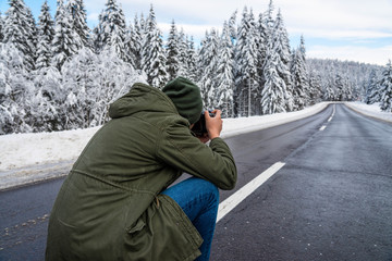 Young unidentifiable photographer taking outdoor images on slippery asphalt road at wintertime.