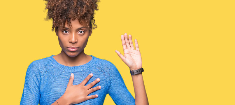 Beautiful young african american woman over isolated background Swearing with hand on chest and open palm, making a loyalty promise oath
