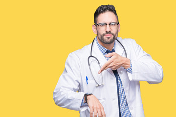 Handsome young doctor man over isolated background In hurry pointing to watch time, impatience, upset and angry for deadline delay