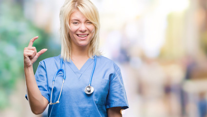 Young beautiful blonde doctor woman wearing medical uniform over isolated background smiling and confident gesturing with hand doing size sign with fingers while looking and the camera