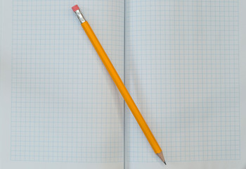 Note book and pencil. a pencil on a white paper in a cell. A simple pencil on a notebook in the cell. School supplies.