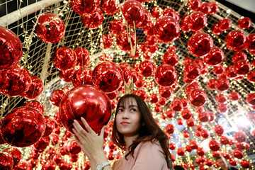 A woman poses for a photo with Christmas ornaments as she celebrates Christmas in Bangkok