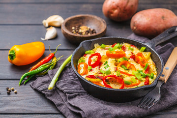 Traditional fritatta with peppers and potatoes in a cast iron pan. Dark wooden background