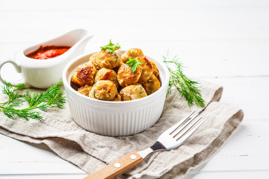Healthy chicken meatballs with greens and tomato sauce on white background.