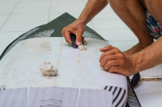 Anonymous  surfer cleaning his surfboard. Removing old wax with a waxcomb. Get ready for surfing. Surf lifestyle.