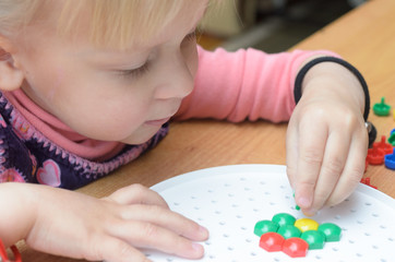A little girl collects a colorful mosaic at the table.